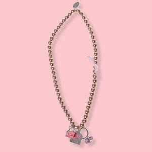 Collar de perlas blancas con cinta rosa y charms
